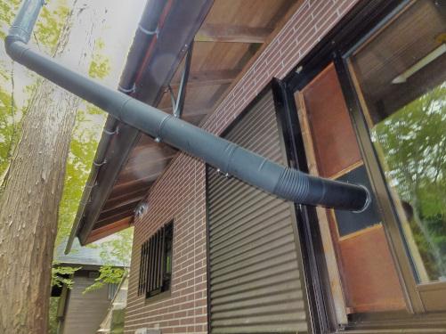 窓から出した煙突を立木に固定する